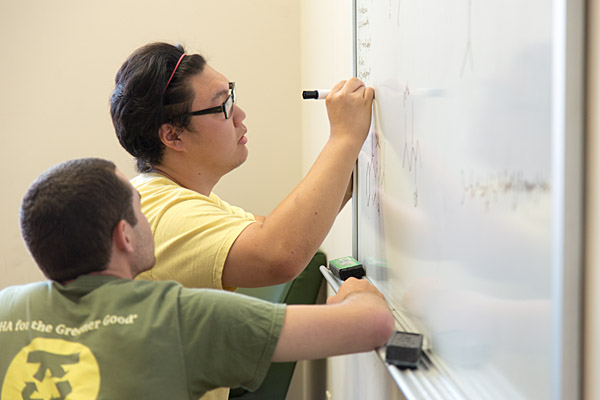 Two students using whiteboard in group study room
