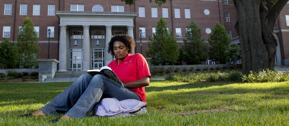 Student studying in the front yard of the MLC