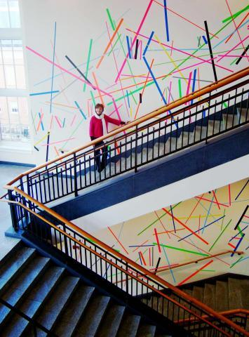 Artist Patricia Van Dalen at her multicolored linear installation on MLC central staircase