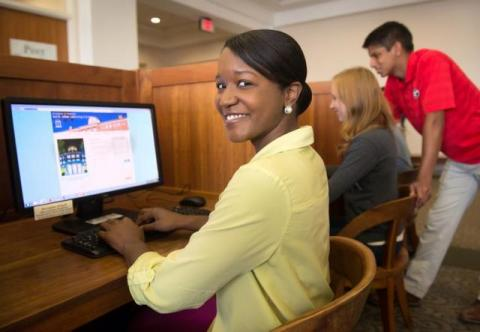 Smiling student using computer lab